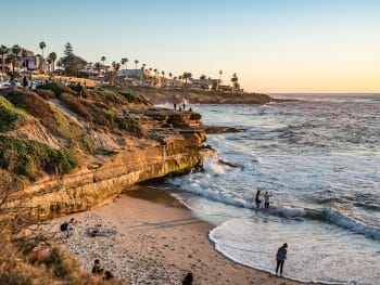 Orange sandstone cliffs in La Jolla with small beach during sunset