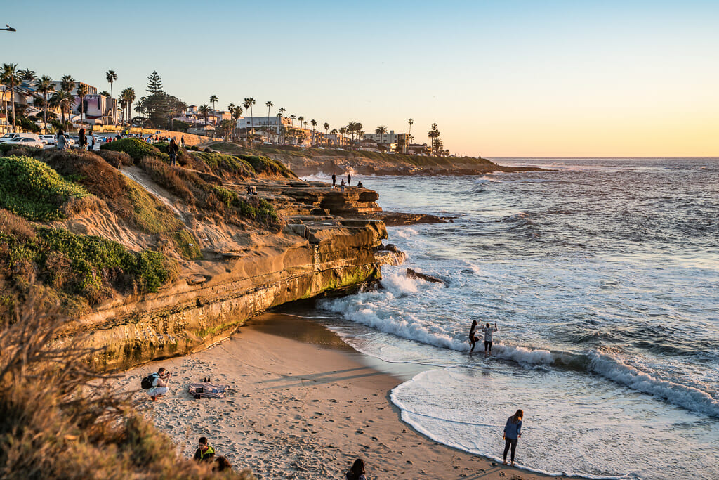 Orange sandstone cliffs in La Jolla with small beach during sunset