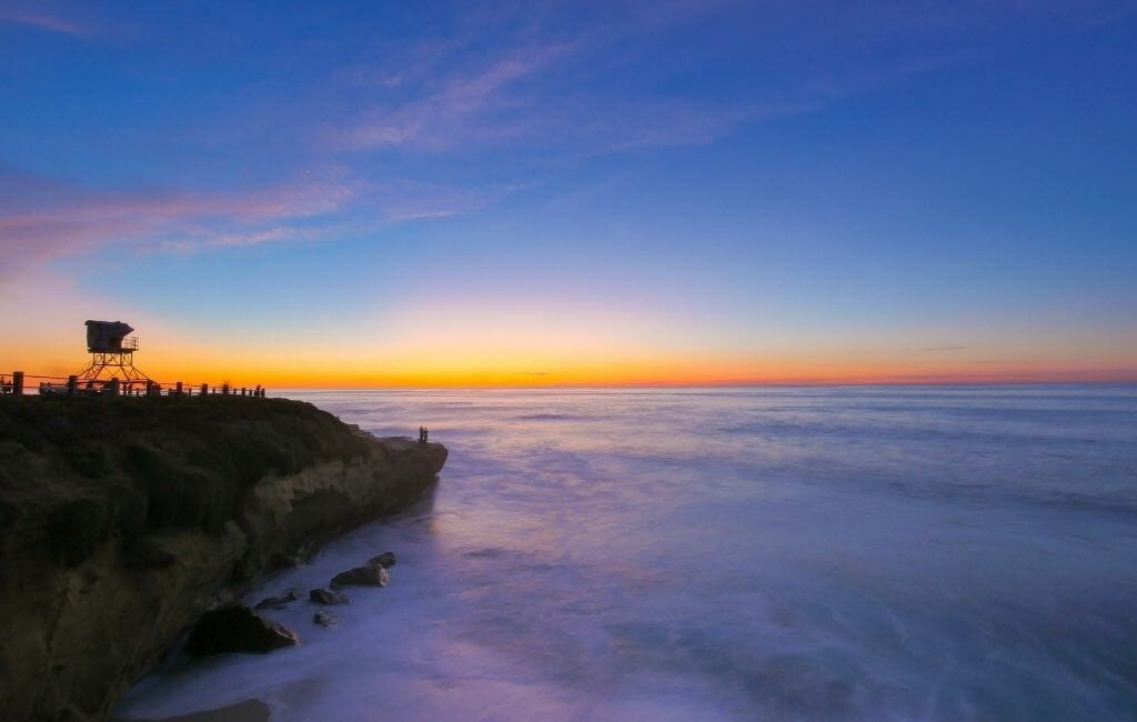sunset over the pacific in La Jolla with sandstone cliffs on the left with a lifeguard tower on top