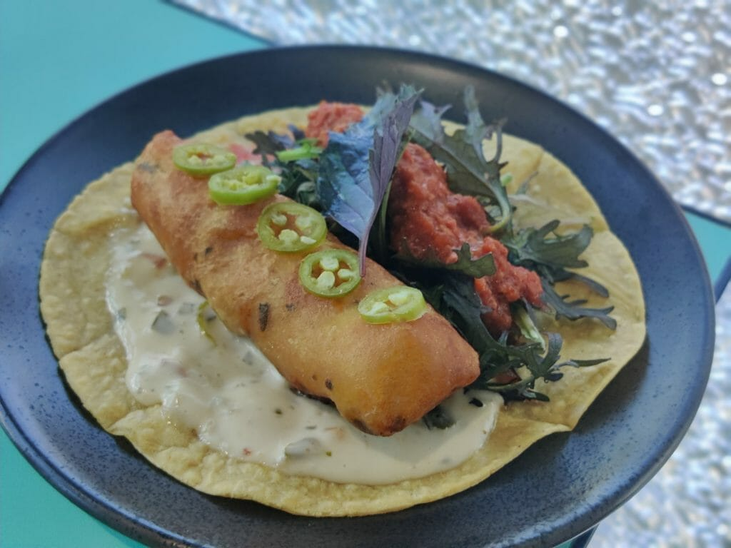 Fish taco on a dark plate on a turquoise table