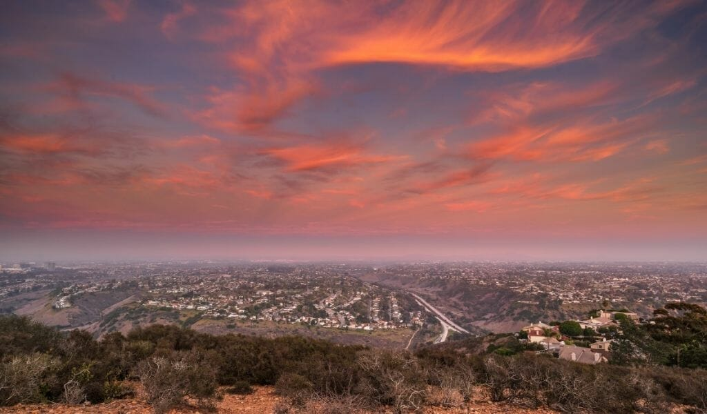 Views from Mount Soledad over La Jolla suburbs during sunset with pink/orange clouds on a purple sky