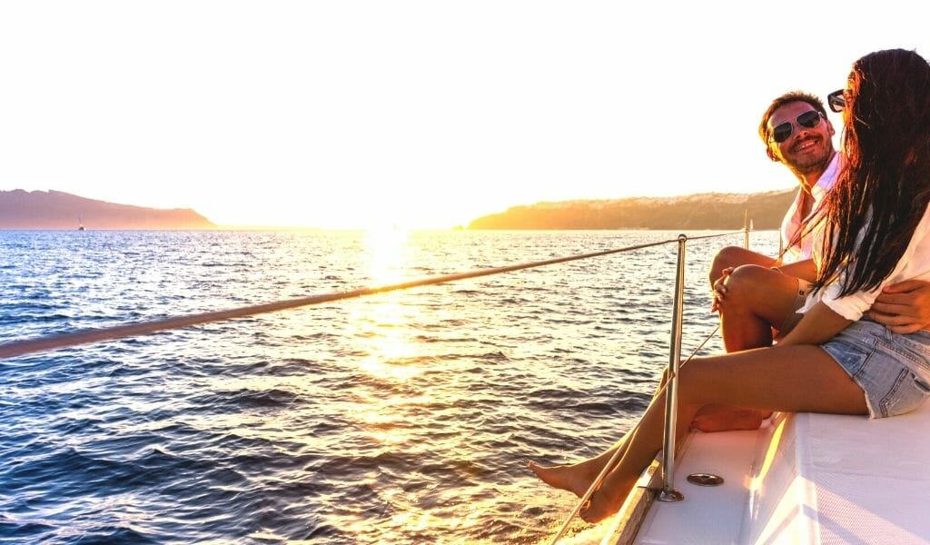 couple sitting on a sailboat watching the sunset