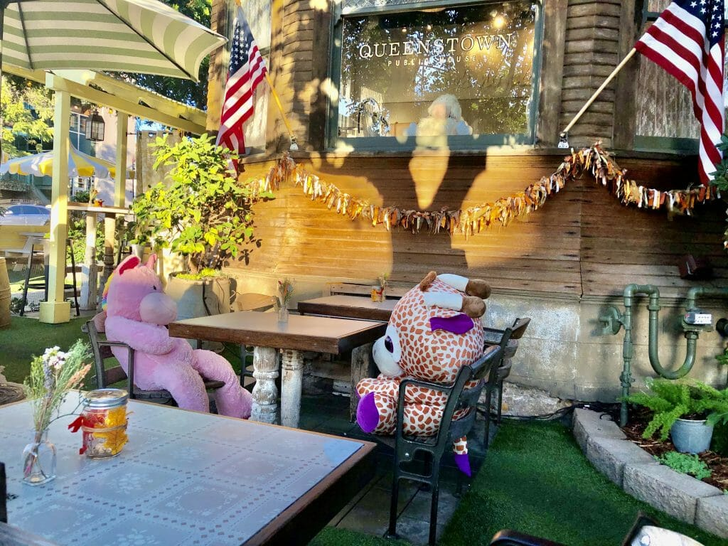 outdoor patio at Queenstown Pub San Diego with stuffed animals seated on every other table for social distancing measure