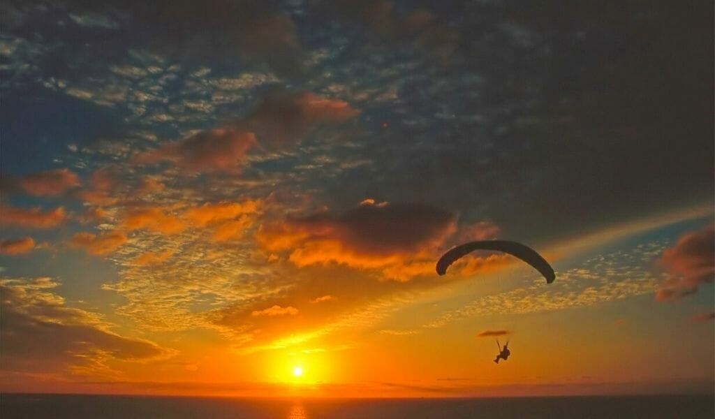 Parachute glider over the ocean during spectacular orange/blue/teal sunset