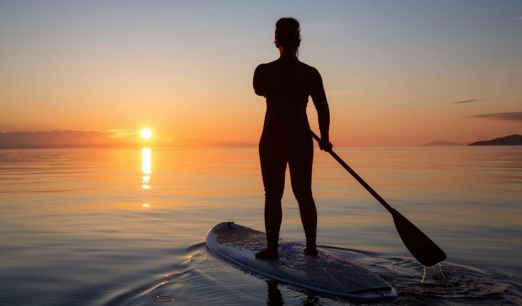 Woman Paddle Boarding on flat lake/ocean during sunset