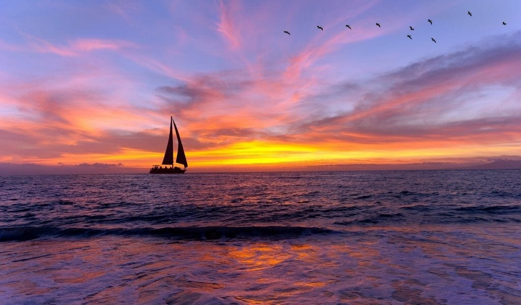 Sail boat near coast during sunset with pink clouds, purple sky, and orange sun
