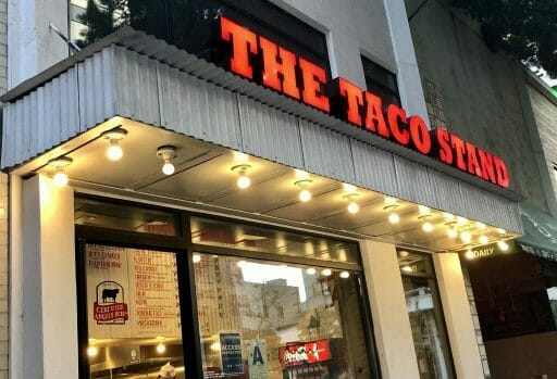 Entrance to The Taco Stand in Downtown with red signage over door and window
