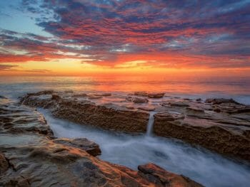 Long exposure sunset photo on Windandsea beach with water flowing over rock formation during colorful sunset