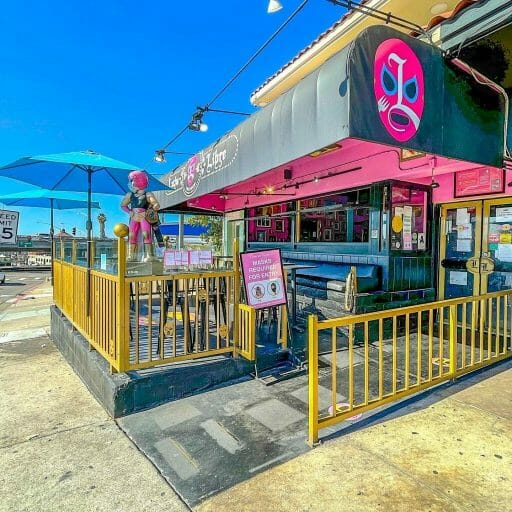 Outdoor patio with yellow fence and pink roof at Lucha Libre - Best San Diego Tacos at Lucha Libre