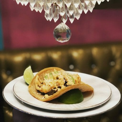 one taco on a stacked plate with a glass chandelier on top and a golden sofa and purple wall in the background