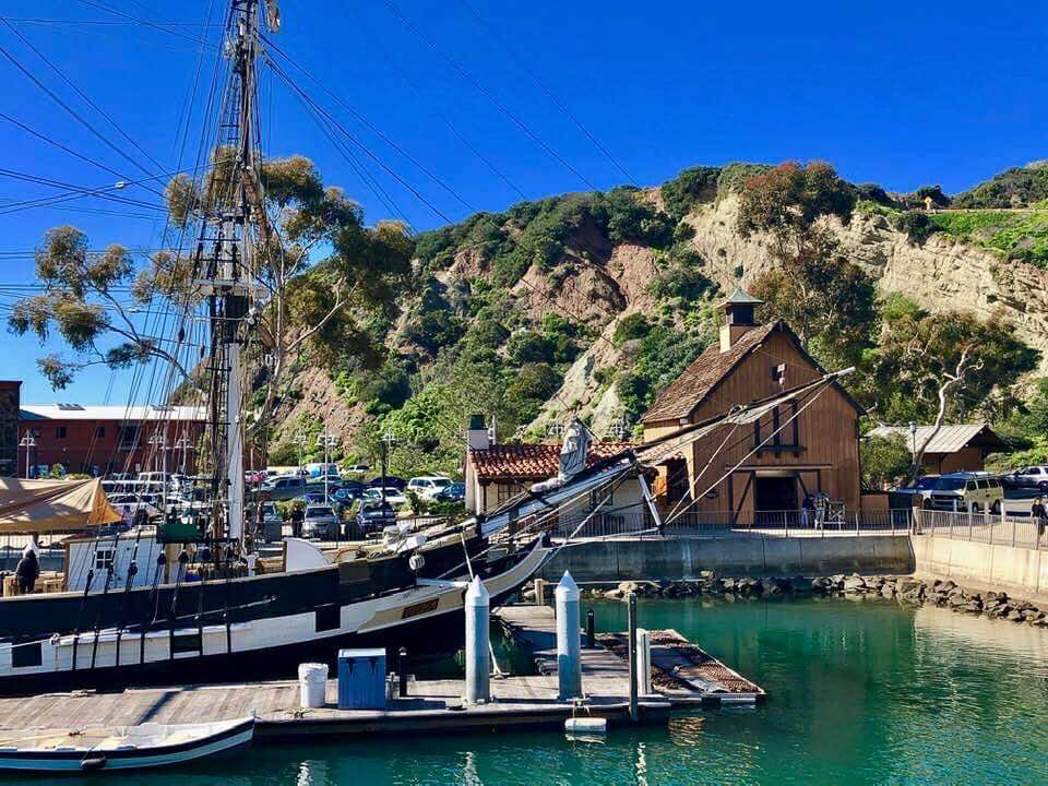Small Marina with large wood Sailboat in front of a wood house in front of a cliff at Dana Point Harbor