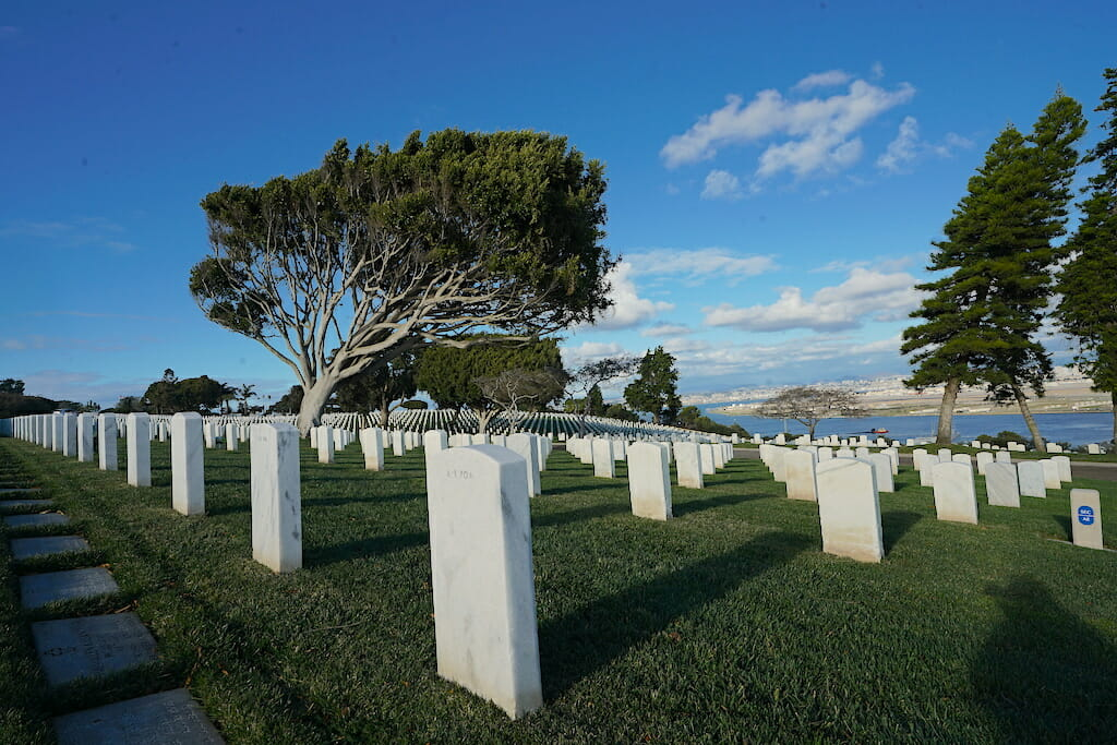 Rows of White grave stones on a sloping meadow overlooking San Diego Bay and Coronado from Fort Rosecrans Cemetary San Diego