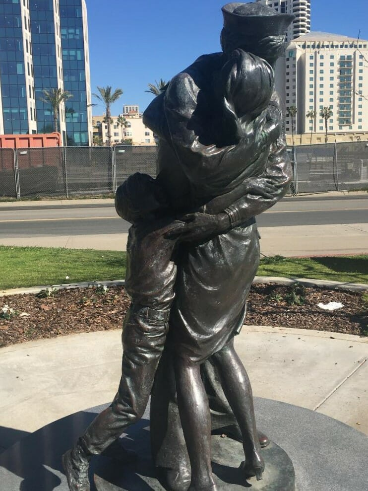 """Metal statue of a soldier hugging his wife and child after returning from service - Statue is called """"Homecoming"""" and is part of the """"Greatest Generation Walk"""" Military Memorial in San Diego"""