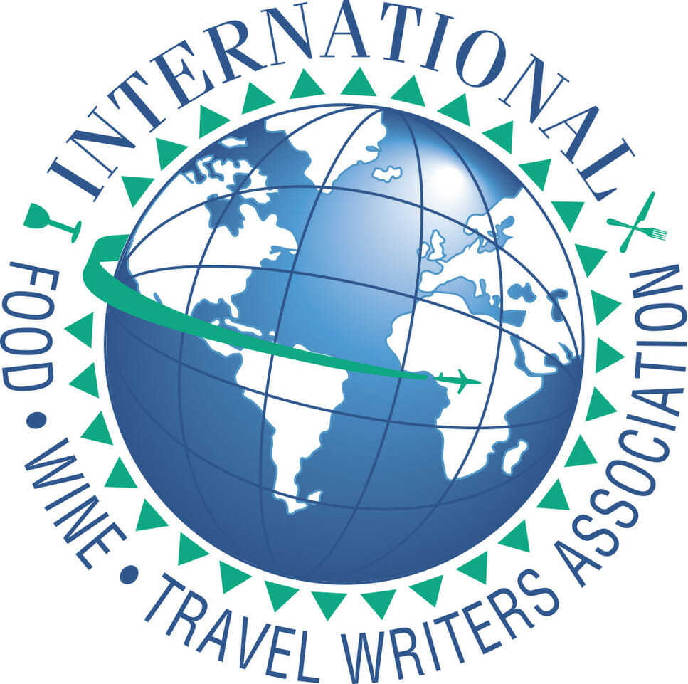 Logo of International Food Wine and travel writers association - blue globe with blue text in capital letters of the name