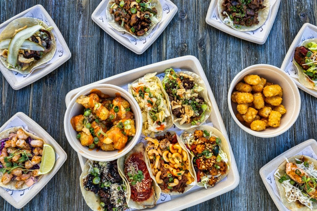 flatlay of various trays and plates with a variety of tacos by Not Not Tacos San Diego