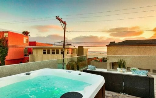 rooftop patio with lounge sofa and hot tub and sunset views to the beach between houses