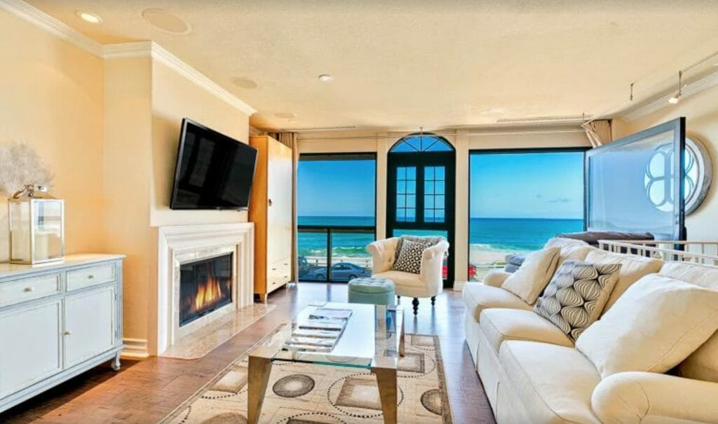 Elegant Oceanfront Vacation Home Living Room with white couch and fireplace and view of the ocean