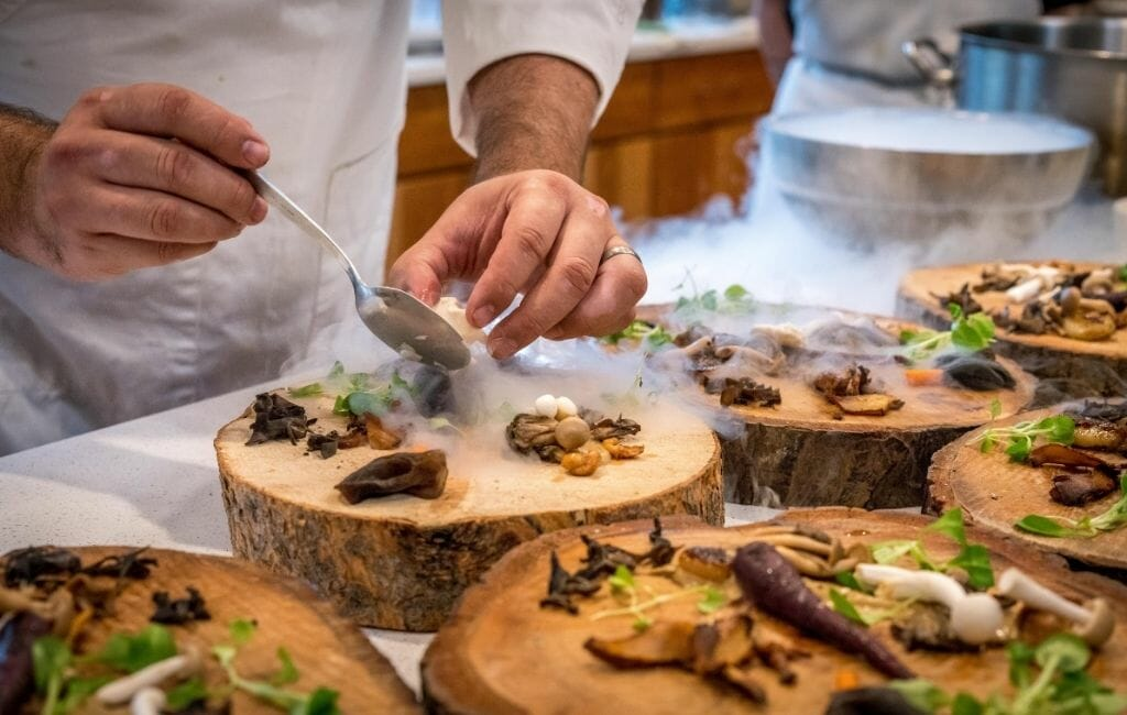 closeup of chef's hands plating food on round wood slabs