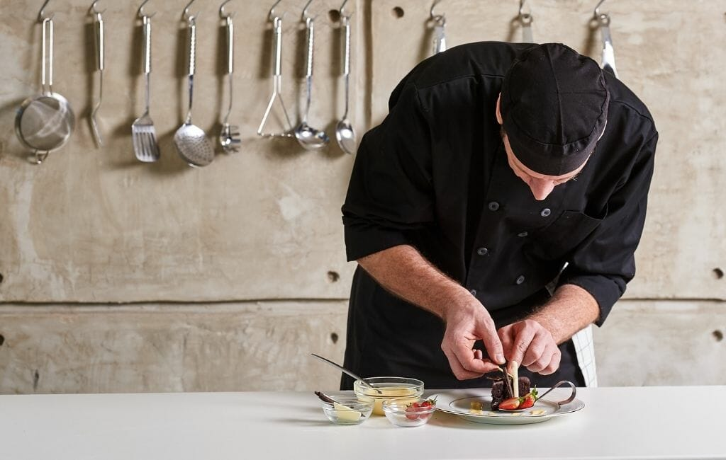 Chef in black uniform plating a plate in a modern kitchen - San Diego Restaurant Week