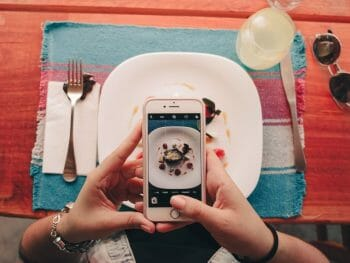 two female hands taking photo of plate of food on a colorful table setting