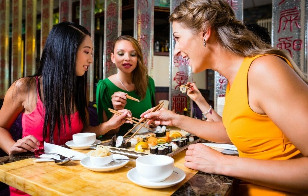 3 young women sitting on a table eating sushi