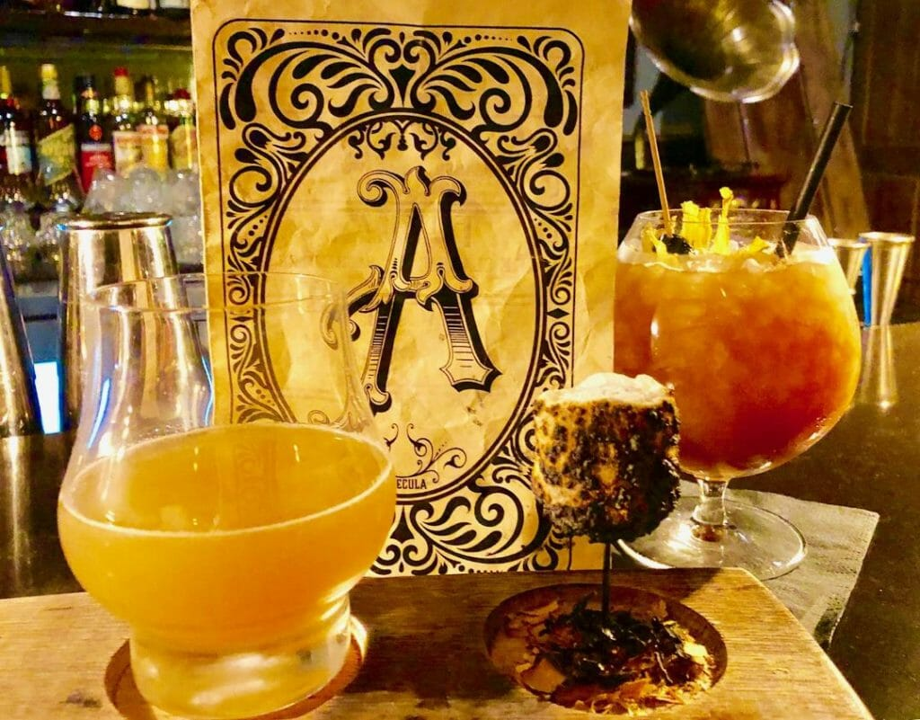 2 craft cocktails in a speakeasy in Temecula - with a menu with a vintage font letter A - things to do in Tememcula