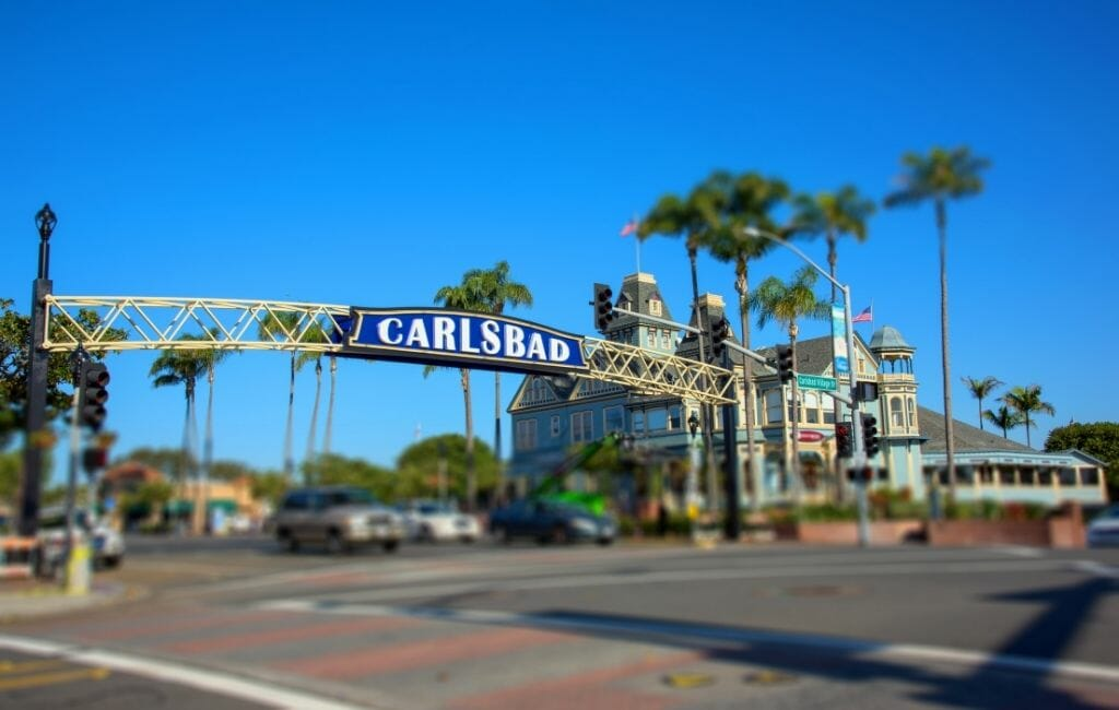 """Blue sign reading """"Carlsbad"""" over the street in Carlsbad Village with a historic Victorian House in the background"""