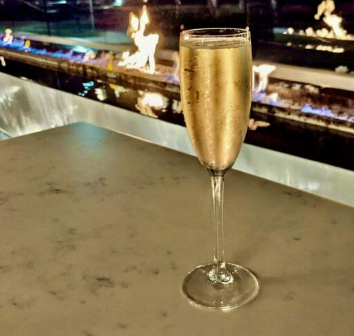 Champagne flute with a gas fire place in the background (blurred) after dark