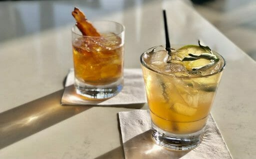 Two yellow/orange cocktails with ice. One with a slice of candied bacon, the other with a sprig of sage and lemon slice