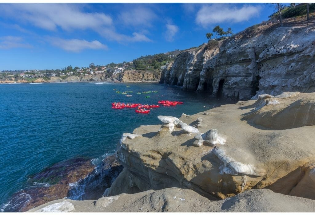 Coastline of La Jolla with Caves on the right and 2 groups with kayakers in the ocean on the left - Kayaking in La Jolla