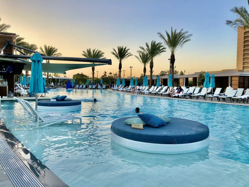 Luxury pool with floats and lounge chairs in shallow water, palm trees and sunset at Pechanga Resort Casino