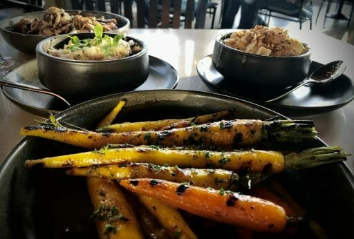 yellow and orange carrots with grill marks and parsley spinkled on top in a dark ceramic bowl