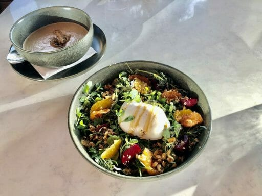 quinoa salad with oranges and beets and a large burrata cheese in the center and a bowl of mushroom soup in the background (blurred)