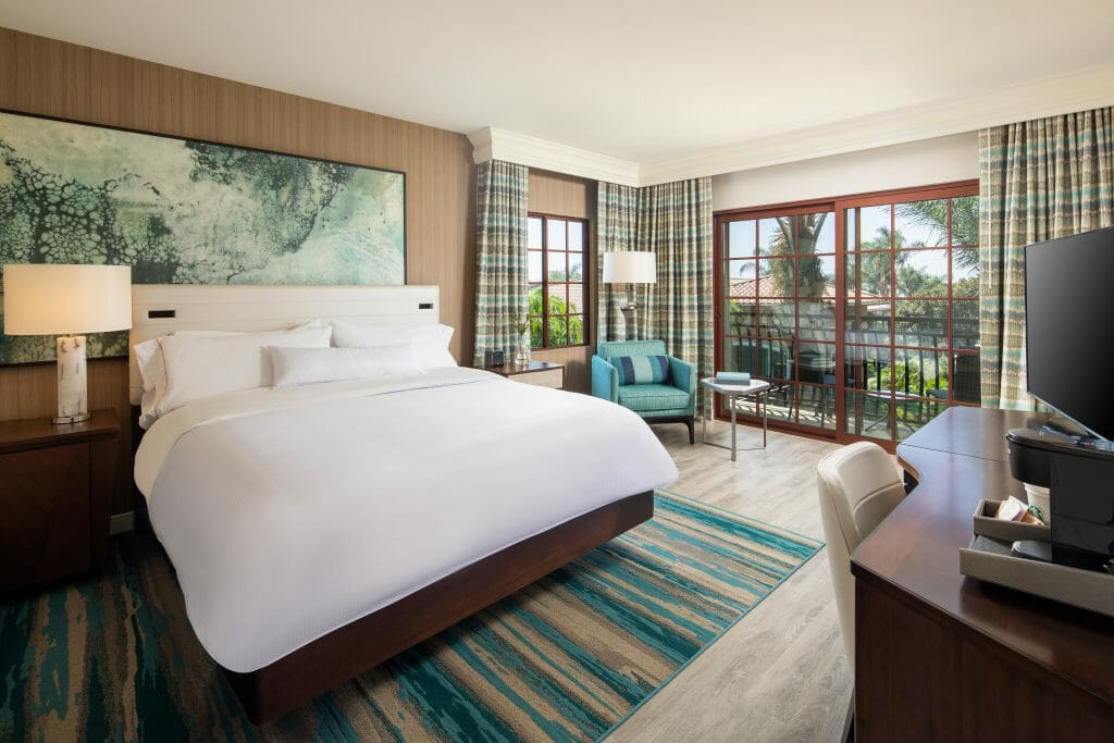 Westin Carlsbad Suite with King Bed and large windows overlooking the palm courtyard