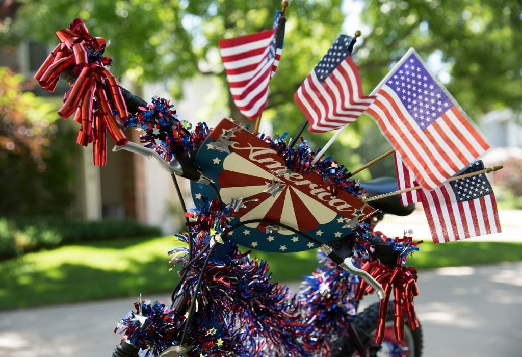 A bicycle decorated with red/white/blue decor and American Flags