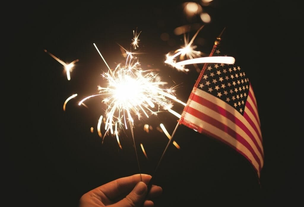 hand holding a mini American flag and a sparkler in the dark