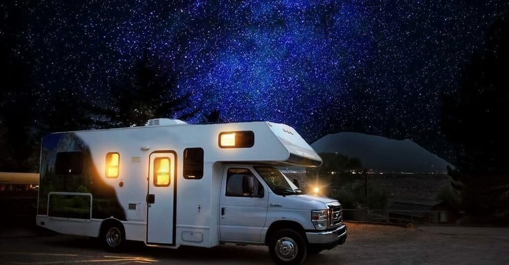 RV with lights on with a stary night sky in the background