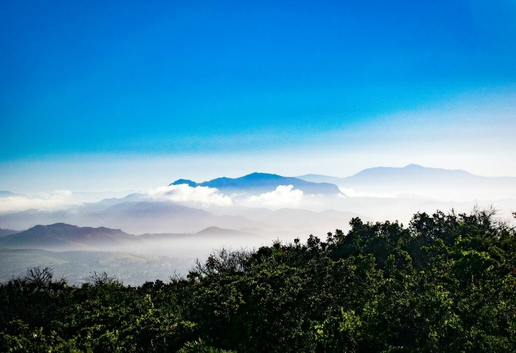 misty mountains in the background with blue sky above and green hills in the foreground - laguna mountains