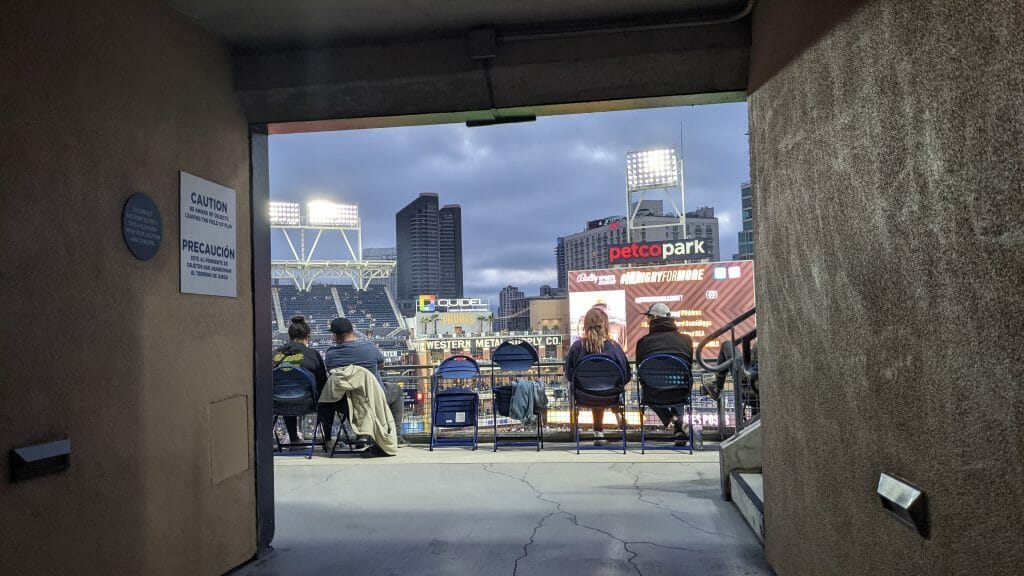 View of petco park from section entrance tunnel with san diego highrises in the background and people sitting on blue folding chairs watching the padres game
