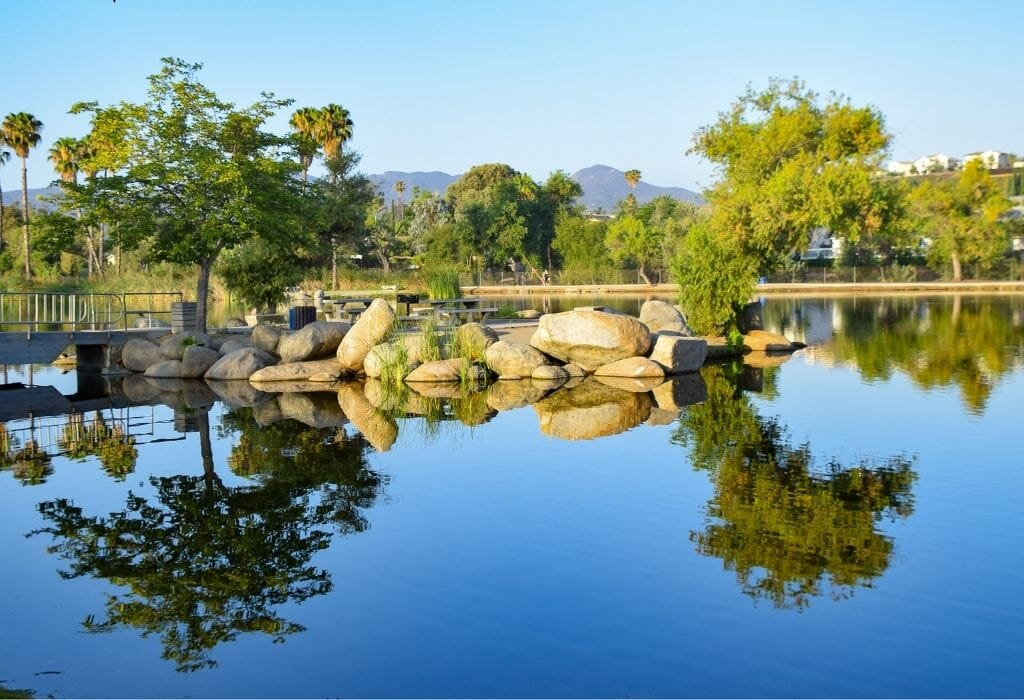still lake with reflections of trees and boulders on a sunny day
