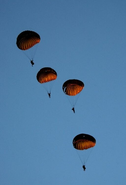 4 soldiers paragliding in formation