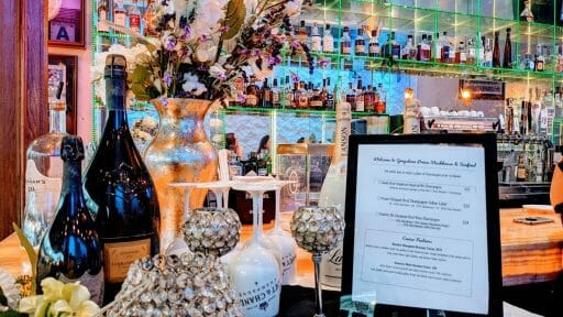 decorated table with champagne bottles, flowers, menu and glasses in front of mirrored bar