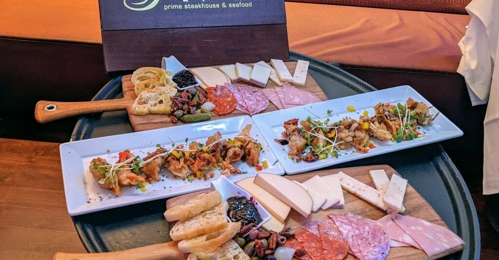 large black serving tray with two charcuterie boards and appetizer samplers with a brown menu with lettering: Greystone