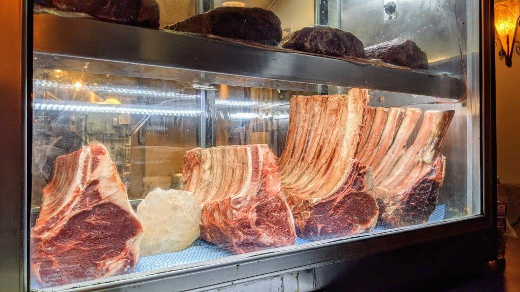 Steaks in a glass fridge on display at Greystone San Diego
