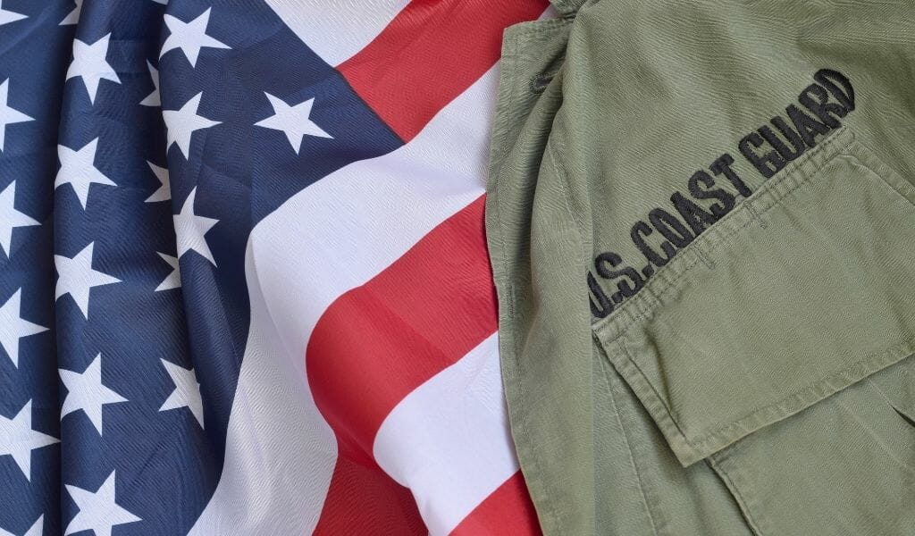 Flatlay of US Flag with olive colored uniform with black lettering: US Coast Guard