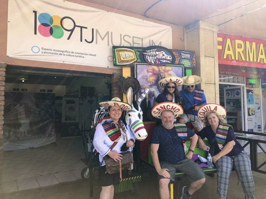 Group of people posing with a fake Tijuana donkey wearing sombreros