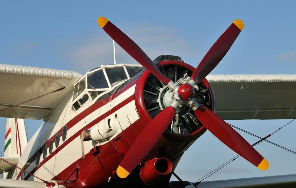 red and white biplane with propellor