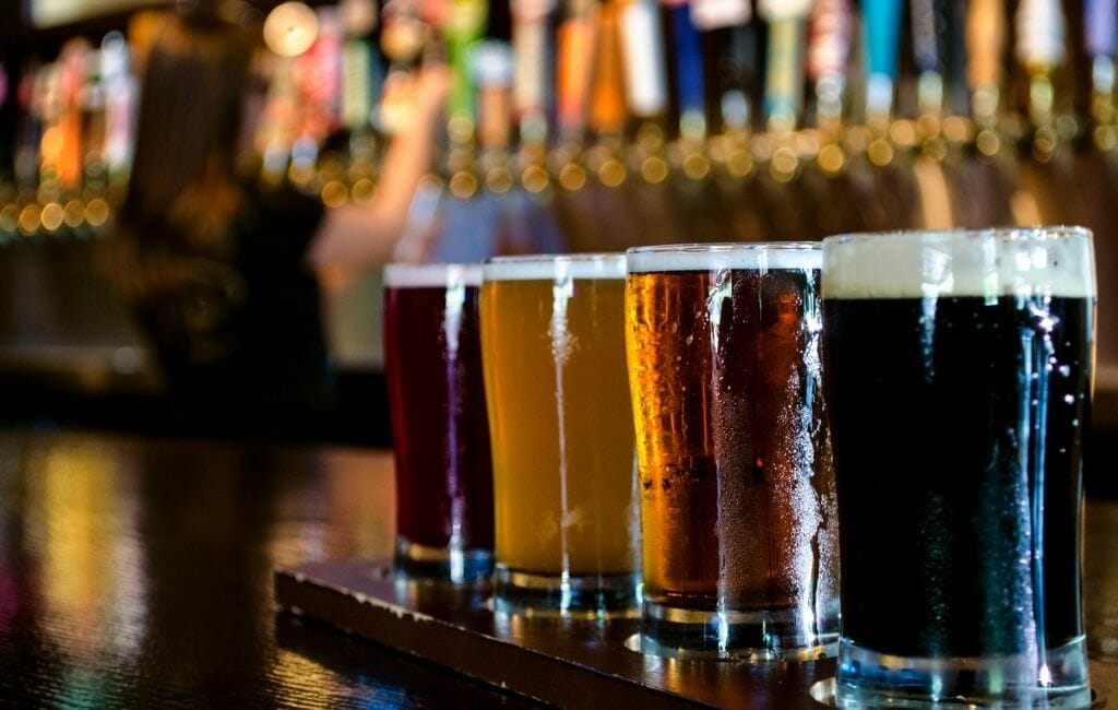 flight of Craft Beers in the foreground with a bar blurry in the background Tijuana-Things To Do in Tijuana