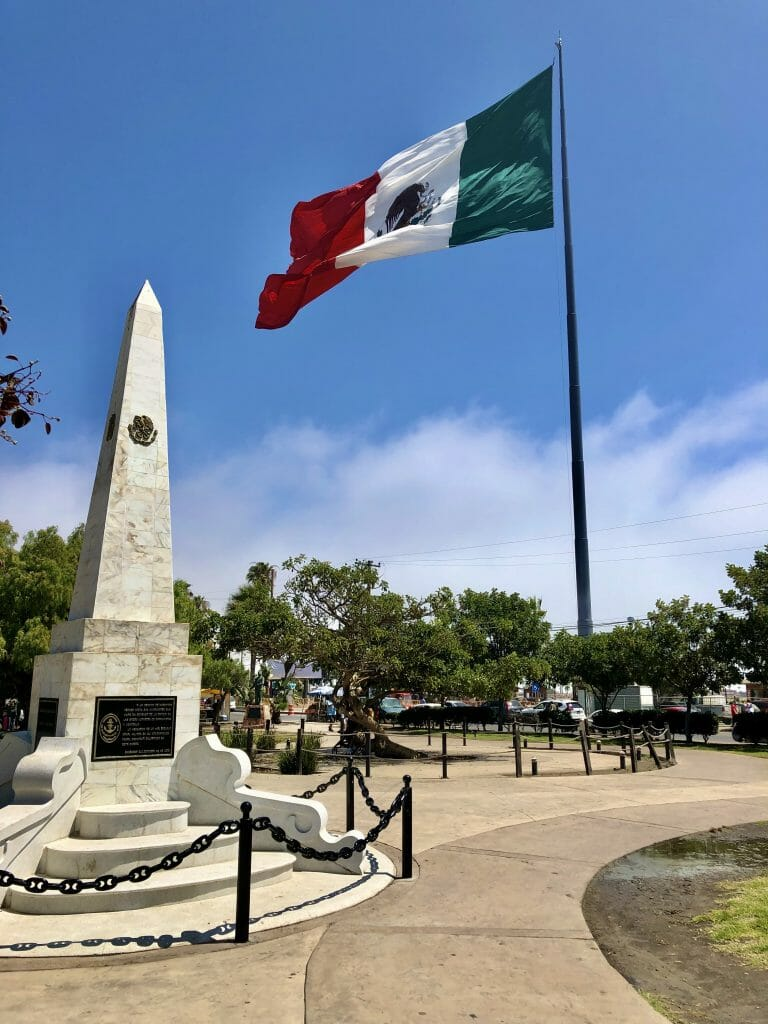City square in Ensenada with white obelisk and large Mexican Flag
