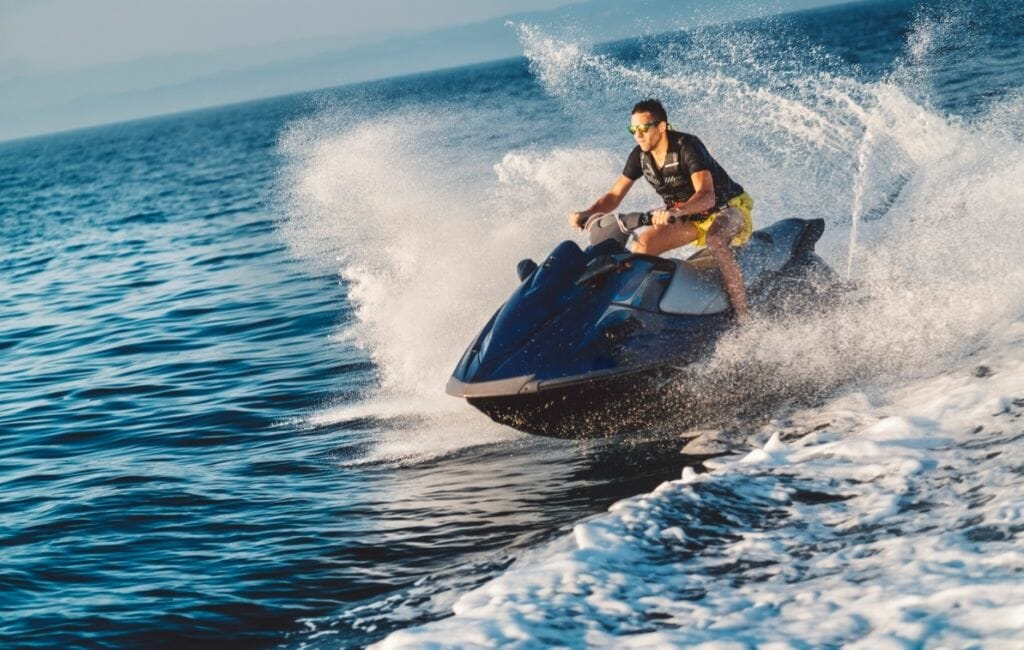 man riding a jet ski on the ocean with waves and water splashing around him